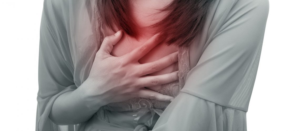 Woman suffering from acid reflux or heartburn, isolated on white background